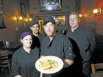 Chef Brian Hall holds a dish of chicken tetrazini at Sideways Classic Grill. With him are, from left, Ashley Bedard, Martin Rocheleau and Ryan Schiestel.  Glenn Ogilvie