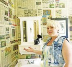 Emily Schrader of Trend Visions in Point Edward shows off hair salon's bathroom, which has been wallpapered in copies of The Sarnia Journal. Glenn Ogilvie