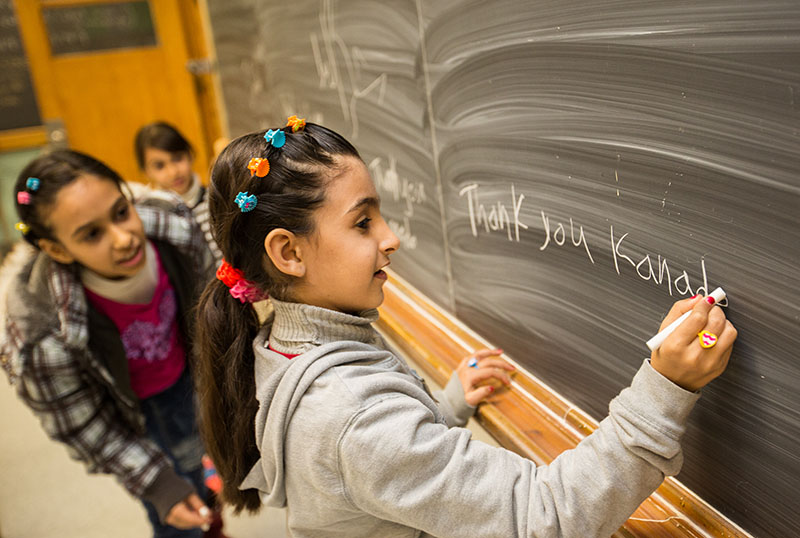 Raghad Al-Khaleel, 8, expresses her family's feelings on a blackboard at the YMCA Learning and Career Centre, while sisters Rooa, and Rahaf look on. Troy Shantz, Special to The Journal