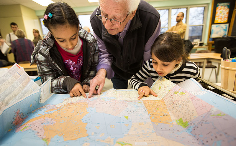 Pastor Harry Mennega looks over a map of Canada with Rooa, 10, left, and Rahaf Al-Khaleel, 6. Troy Shantz, Special to The Journal