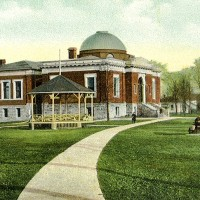 """This coloured postcard from the 1910s shows the Carnegie Library, bandshell and the cannon """"Big Tom"""" in what today is called Veteran's Park. Located at the corner of Christina and Wellington, it was formerly known as Market Square. Dave Burwell Collection, Sarnia Historical Society"""