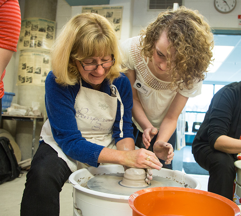The Journal's Cathy Dobson gets a hand from Lambton College paramedic student Amy McDonald while turning an auction entry for Empty Bowls on March 31. Troy Shantz