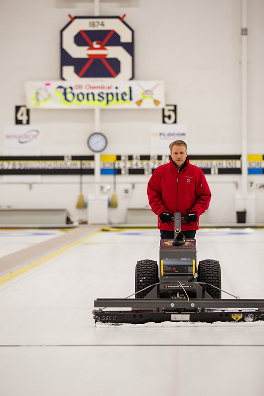 Don Bourque pushes a power scraper over the ice to make it smooth and ready for pebbling. Troy Shantz