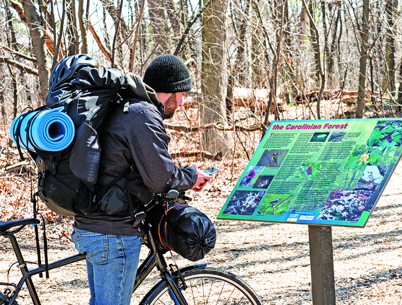 Philipp Czakert, a visitor from Germany, reads an information panel about the plants and animals in Tarzanland, the city's prized 22-acre hardwood forest in Canatara Park. The bio-medical engineering student spent a few days in Sarnia last week while on a two month cycle-tour of Ontario and Michigan. Czakert said he uses a phone app to find like-minded travellers and places to stay overnight while on his journey. Glenn Ogilvie