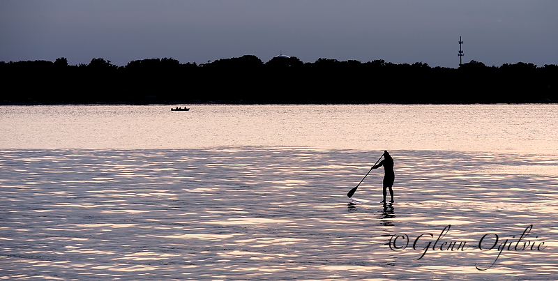 A lone paddleboarder takes in the setting sun while on a cruise on Lake Huron, with Port Huron in the background. Glenn Ogilvie