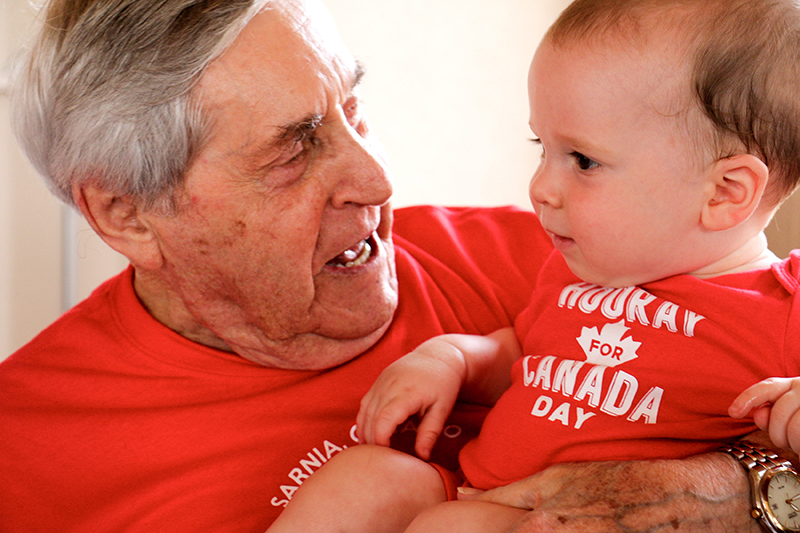 Elie Bergeron, 93, hangs on to 11-month-old Andrew Jeffrey during Storytime at Vision Nursing Home.  Tara Jeffrey